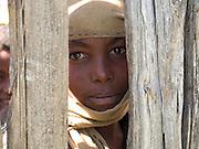 A boy looks through the fence on a farm in Kotoba, Ethiopia