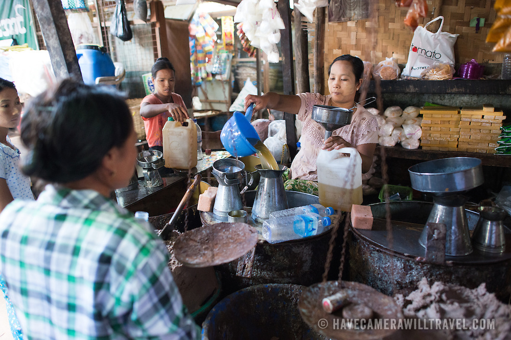 NYAUNG-U, Myanmar - A woman measures out cooking oil for a customer at Nyaung-U Market, near Bagan, Myanmar (Burma).