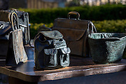 "Bronze table-top sculptures of bags by Koko Rico titled ""Viajeros/Bidaiariak Izenekoa"" at Laguardia in Rioja-Alavesa, Spain"