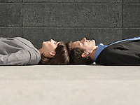 Business man and woman lying on ground head to head side view