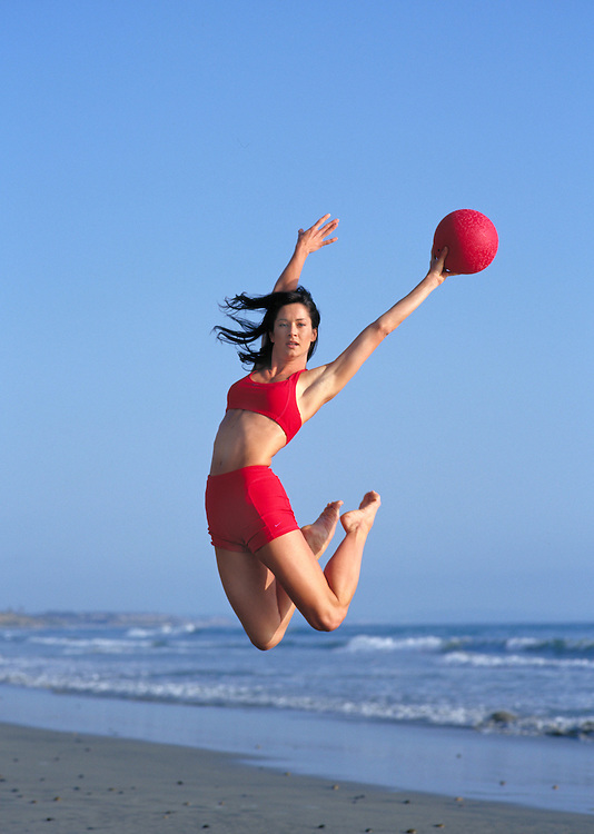 Woman leaping in the air with red ball on Carlsbad State Beach, CA.