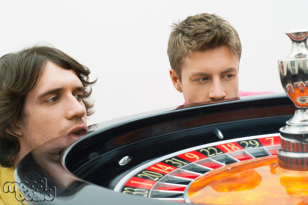 Two hopeful  young men crouching at roulette wheel watching spin close up
