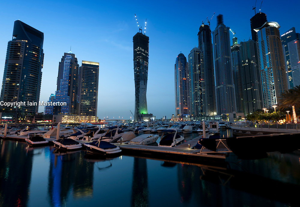 Evening view of new Dubai Marina with yachts and high rise apartment towers to rear in Dubai United Arab Emirates , UAE