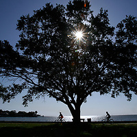 St. Petersburg, Fla. -- Apr. 22, 2007  -- Two bicyclists ride along the water as the sun rises over Bayfront Park in the Old Historic Northeast neighborhood in St. Petersburg, Fla., on Sunday, April 22, 2007.  Created in 1911, the waterfront neighborhood features mostly single-family houses in a vast array of architecture styles, and is the second largest neighborhood behind Key West on the National Register of Historic Places.