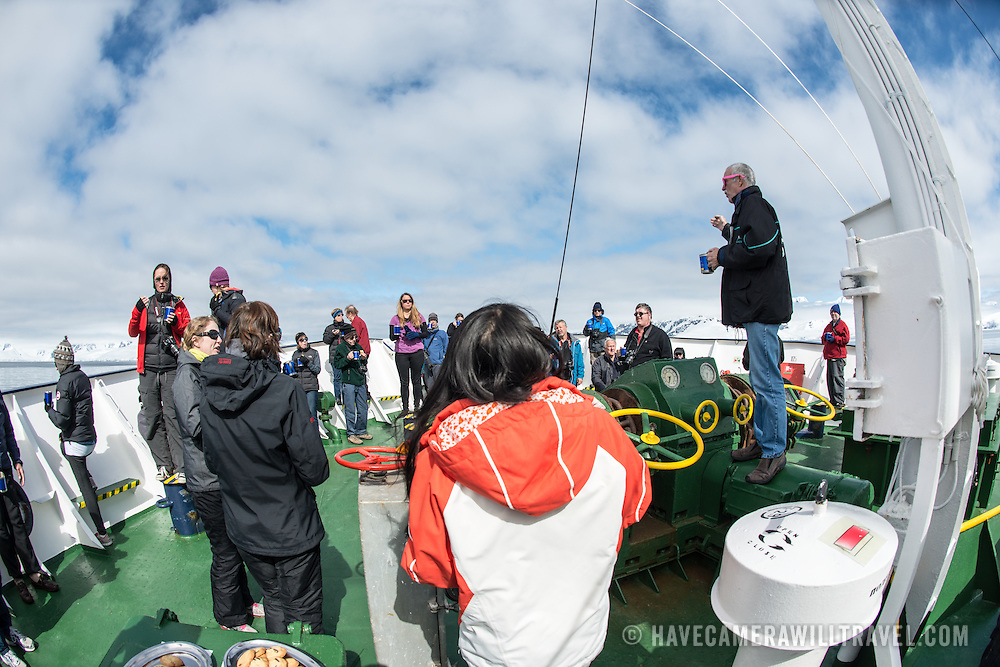 Passengers and crew gather for outdoor afternoon tea on the deck of the Polar Pioneer in Fournier Bay in Antarctica. The Polar Pioneer is a Russian ice-strengthened ship operated by Australian company Aurora Expeditions.