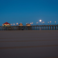 The full moon lights the sky behind the Huntington Beach Pier shortly before sunrise.