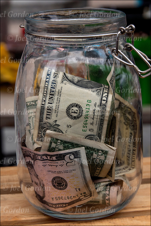 Money in glass jar (tips)at street fair / block party in NYC.