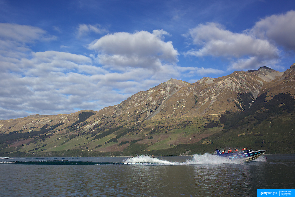 A Dart River Jet Boat on Lake Wakatipu at Glenorchy..Glenorchy is a small settlement nestled in spectacular scenery at the northern end of Lake Wakatipu in New Zealand's south Island. It is approximately 45 kilometres by road or boat from Queenstown, the nearest large town..Glenorchy is a popular tourist spot, close to many tramping tracks. It lies near the borders of Mount Aspiring National Park and Fiordland National Park. The local scenery received worldwide attention when it was used as one of the settings in the first of Peter Jackson's Lord of the Rings films. Glenorchy is the home of  Dart River Jet Safaris. The  unique adventure combines exhilarating wilderness jet boating with unique Funyak inflatable canoes used to explore the magnificent World Heritage wilderness within Mt Aspiring National Park. Professional guides take participants through dramatic landscapes, paddling along channels of the glacier fed Dart River's braided river system as well as along hidden side streams, rock pools and dramatic chasms. Glenorchy, New Zealand. 13th April 2011. Photo Tim Clayton..