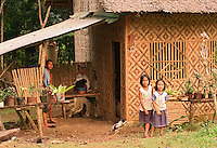 A man and two young girls standing outside their home, a traditional Bahay Kubo (house), Bohol, Philippines..