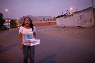 A woman walks down the street on Tuesday, Apr. 7, 2009 in Ventanilla, Peru.