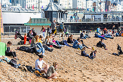 © Licensed to London News Pictures. 24/02/2019. Brighton, UK. Members of the public relax on the beach in Brighton and Hove as sunny weather is hitting the seaside resort. Photo credit: Hugo Michiels/LNP