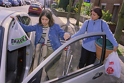Teenage girl with physical disability preparing to get into car holding bag of shopping,