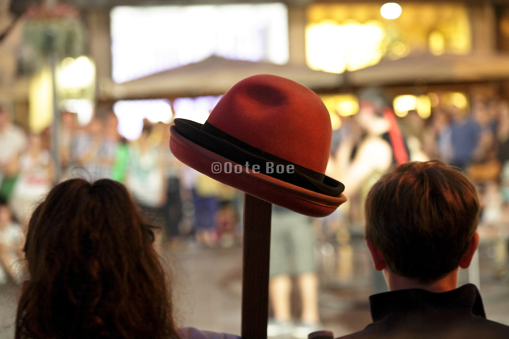 hat on pole with people standing next to it