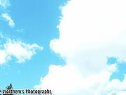 A light blue sky & a puffy cloud together.