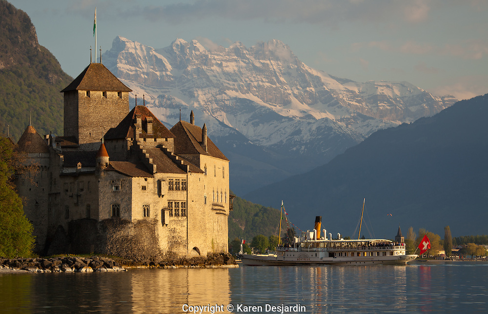 A cruise boat stops at the Chateau du Chillon on Lake Geneva (Lac Léman), near Montreux, Switzerland. The peaks of the Dents du Midi are visible in the background. The castle of Chillon was made popular by Lord Byron, who wrote the poem The Prisoner Of Chillon (1816) about François de Bonivard, a Genevois monk and politician who was imprisoned there from 1530 to 1536; Byron also carved his name on a pillar of the dungeon. The castle is one of the settings in Henry James's novella Daisy Miller (1878). http://www.gettyimages.com/detail/photo/chateau-chillon-and-the-dents-du-midi-high-res-stock-photography/470803981
