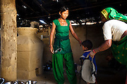 Pramila Tharu, 15, does household chores as her mother-in-law brings her 2 year old daughter Prapti to her in Bhaishahi village, Bardia, Western Nepal, on 29th June 2012. Pramila eloped and married at 12 and gave birth to Prapti at age 13. She delivered prematurely on the way to the hospital in an ox cart and her baby weighed only 1.5kg at birth. In Bardia, StC works with the district health office to build the capacity of female community health workers who are on the frontline of health service provision like ante-natal and post-natal care, especially in rural areas. Photo by Suzanne Lee for Save The Children UK