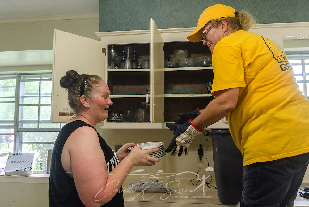 Southern Baptist Disaster Relief volunteer Kim Rowland, a member of East Dublin Dayspring Worship Center in East Dublin, Ga., cleans out a kitchen cabinet with homeowner Karen Johnson, of Immaculate Conception Church, Aug. 26, 2016, in Denham Springs, La. Rowland, along with other SBDR Georgia volunteers, is at Johnson's home this week, helping her mud out the flood-damaged house. Johnson is among thousands of Louisiana residents affected by a mid-August flood. (Photo by Carmen K. Sisson)