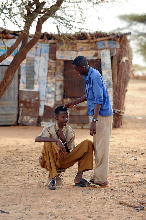 Abdiwah Hassan Abdi (17) getting his hair cut by Mowhid Mahmod Moge (barber) at Belet Amin, a camp for internally displaced Somalis near the border with Kenya. The camp was set up for people fleeing the fighting in Somalia in 1997. 26/6/2008