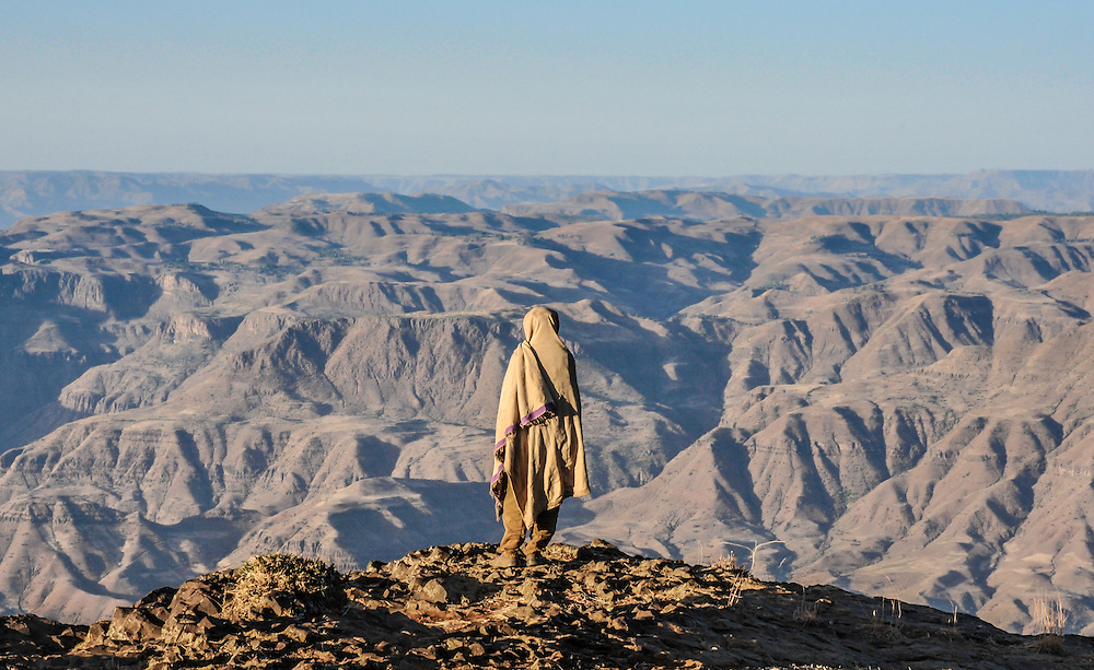 Man with a cloth around him staring at the rugged hills of Northern Ethiopia.