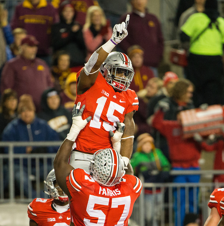 Ohio State University running back Ezekiel Elliott (15) is held up by offensive lineman Chase Farris (57) after Elliott rushed for a touchdown during the first half of a NCAA Division I football game between Ohio State University and the University of Minnesota at Ohio Stadium on November 7, 2015 in Columbus, Ohio. (Dustin Satloff)