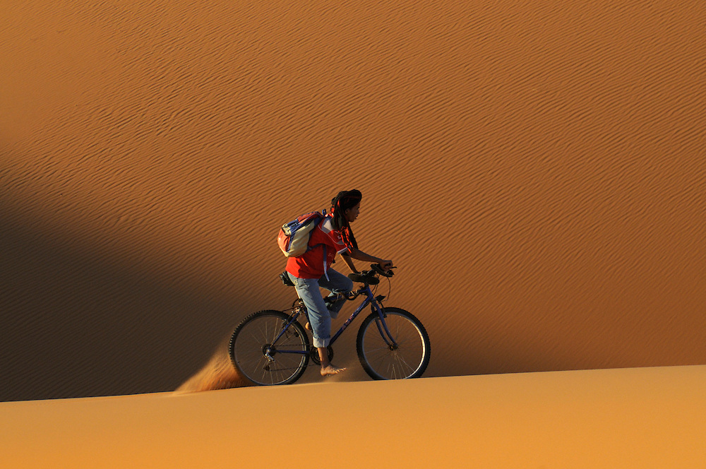 A man is cycling with his mountainbike through a desert. Merzouga. Morocco. Africa.
