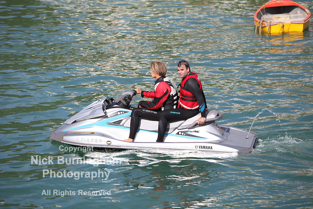 Newquay Harbour, Newquay, Cornwall, August 6, 2015.  High tide and a sunny morning brings a range of tourist activities to Newquay Harbour. Tourists enjoy trips out on a powerful jetski