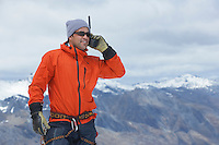 Hiker using walkie-talkie on mountain peak