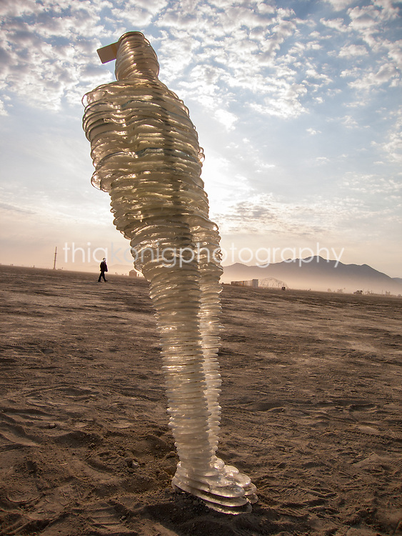 A layered glass art installation of a man leaning backwards on the Playa, Black Rock City, Burning Man.