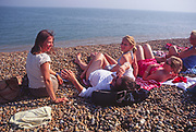 AYBR67 Woman friends and children sunbathe and chat on shingle beach summer England