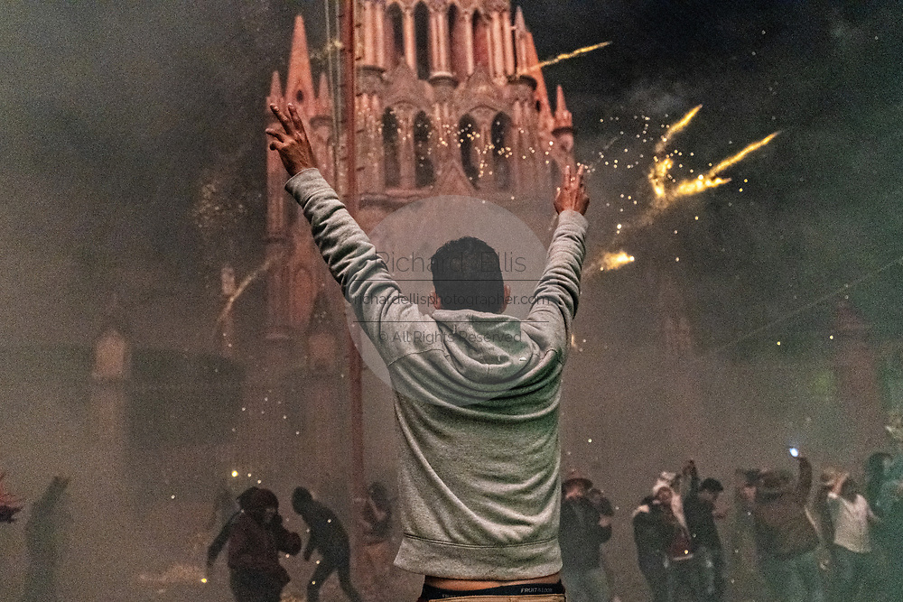 A Mexican man holds his arms up at the San Miguel Archangel church during a barrage of sky rockets at the Alborada festival September 29, 2018 in San Miguel de Allende, Mexico. The unusual festival celebrates the cities patron saint with a two hour-long firework battle at 4am representing the struggle between Saint Michael and Lucifer.