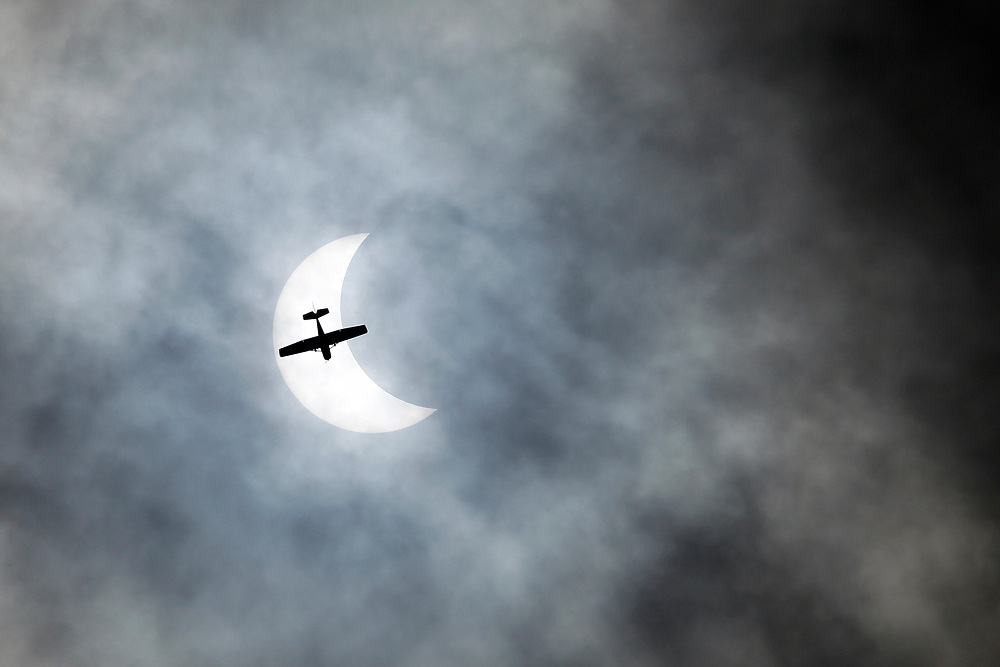 A small plane passes under the partially eclipsed sun Monday in Isle of Palms. Andrew Knapp/Staff