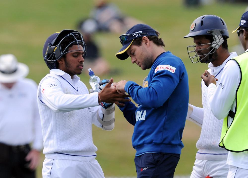 Sri Lanka's Kusal Mendis receives treatment for an injured finger against New Zealand on day three of the second International Cricket Test, Seddon Park, Hamilton, New Zealand, Sunday, December 20, 2015. Credit:SNPA / Ross Setford