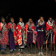 The Stars Foundation visiting S.A.F.E in the Loita Hills near the Tanzanian border in Kenya...It is mainly Maasais who live in the Loita Hills up above the Serengeti plains. They live in small villages and communities called bomas and live mainly of raising and selling live stock such as cattle and goats. Its a very remote region in Kenya, hard to get to without a four wheel drive with very little infrastructure and up till 2010 no mobile phone network. The Maasais are well known though out Kenya and the world for their colorful clothing and their way of keeping their old traditions alive...It is Wilson's wedding party and his village is full of visitors. Wilson is also a member of the S.A.F.E theatre group. Here weddng guests are enjoying a performance by S.A.F.E about Female Genital circumcision. S.A.F.E.  is a charity which educates children and young people about life skills and how to protect themselves from HIV and other STIs through performance. They also do performances about Female Genital Mutilation, an old tradition amongst the Maasais in Loita and a very brutal and controversial custom which S.A.F.E is trying to eradicate. There is no electricity other than a generator which runs two lights used for the show.