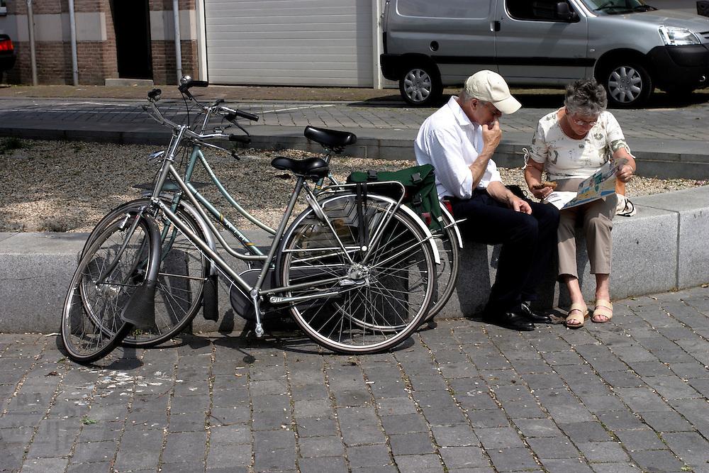 Een man en een vrouw bekijken tijdens een fietspauze in het centrum van Nijmegen een brochure.<br /> <br /> A man and woman are looking at a brochure during a stop at the center of Nijmegen.