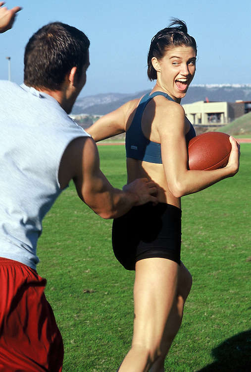 Lifestyle image of young couple playing football in San Diego, CA.