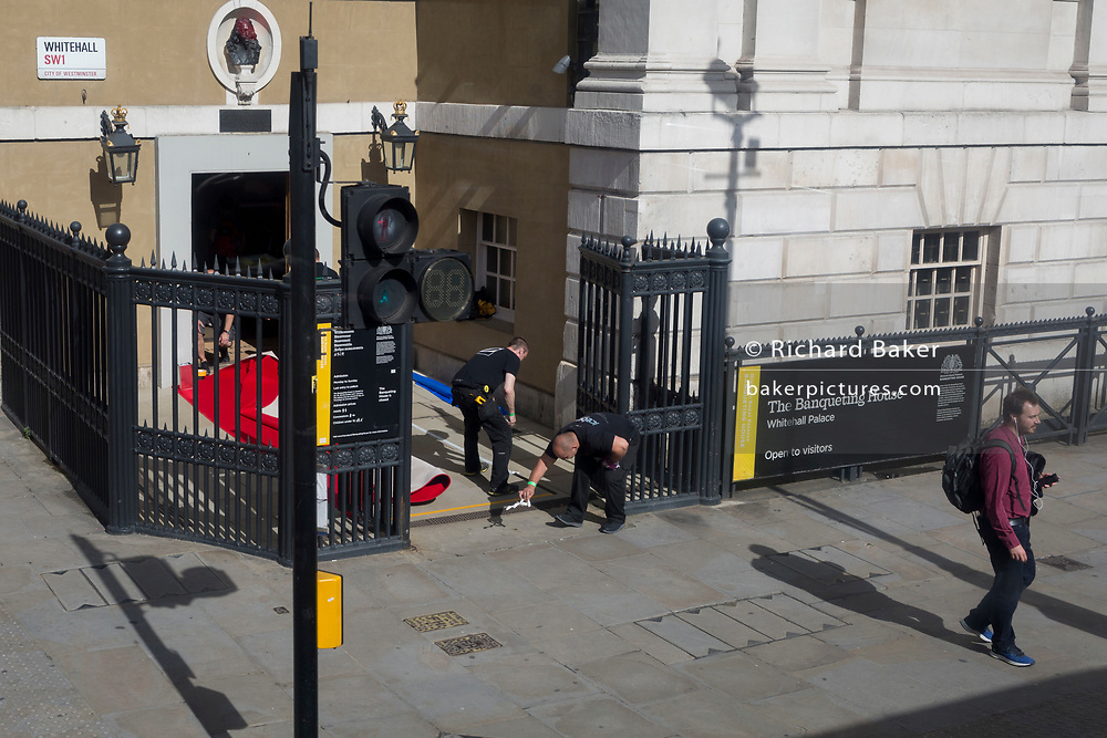 Ahead of a special evening event, workmen lay the red carpet at the entrance of the Banqueting House Whitehall Palace, on Whitehall, on 15th June 2019, in London, England.