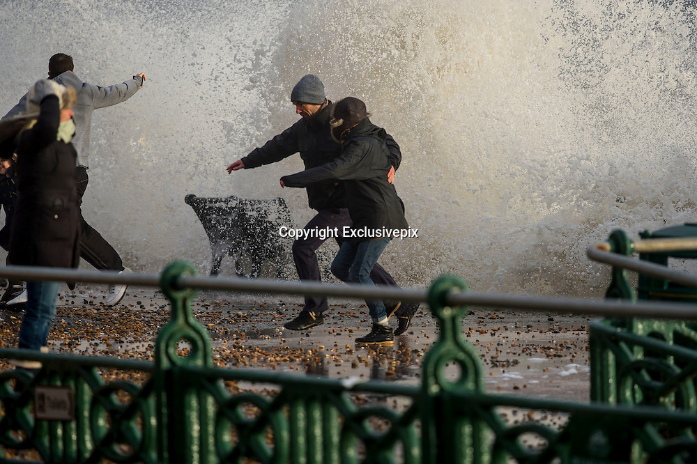 Winds and storms hit Britain<br /> Gale force winds, rain and tidal surges continue to batter the UK coastlines today. Scenes from Brighton and Hove, Sussex, UK. A man dodges large waves in Hove, Sussex, UK<br /> &copy;Exclusivepix