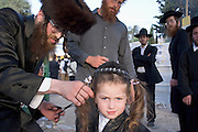 Israel, Galilee, Mount Meron, first Haircut Ceremony to 3 year old boys at Mount Meron during the lag b'omer celebrations at mount Meron. Lag B'Omer is a day for bonfire celebrations. The most famous is held at the village of Meron, near the northern city of Safed. Shimon Bar Yochai is said to be buried there, and huge crowds gather at his tomb for this very happy celebration. Since the days preceding Lag B'Omer were traditionally considered days of mourning, and therefore haircutting and shaving were not permitted, Lag B'Omer became a time for youngsters of 3 years get their first haircut. May 2005