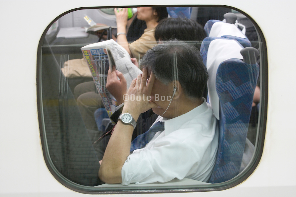 business people sitting inside a Shinkansan train compartment waiting to leave the station Japan