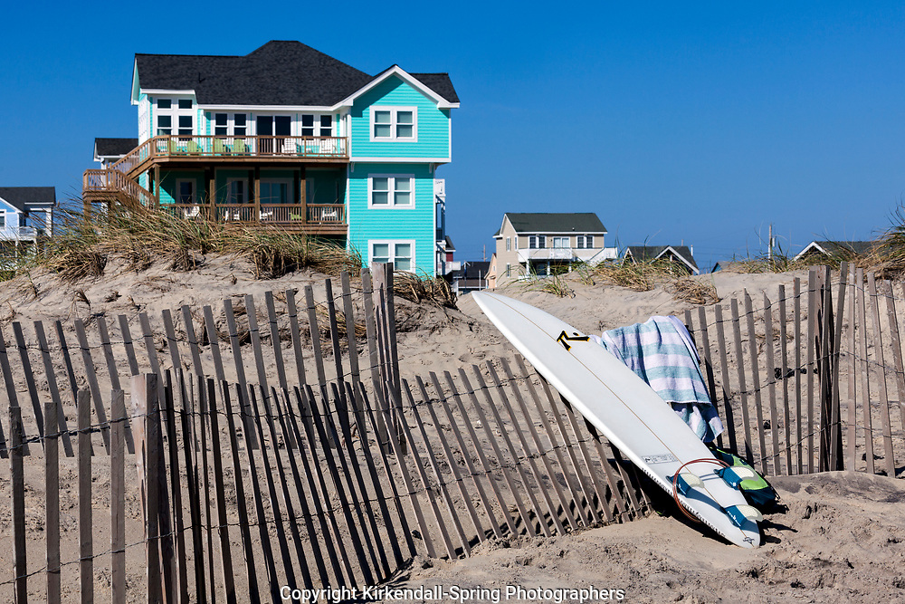 NC00746-00...NORTH CAROLINA - Surfboard, sand fence and beach houses at Rodanthe on the Outer Banks, Cape Hatteras National Seashore.