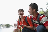 Man embracing woman holding water bottle near ocean