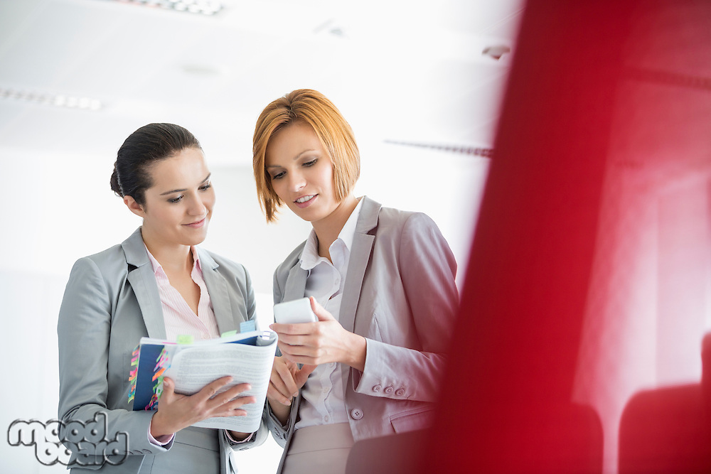 Young businesswomen with book while using cell phone in office