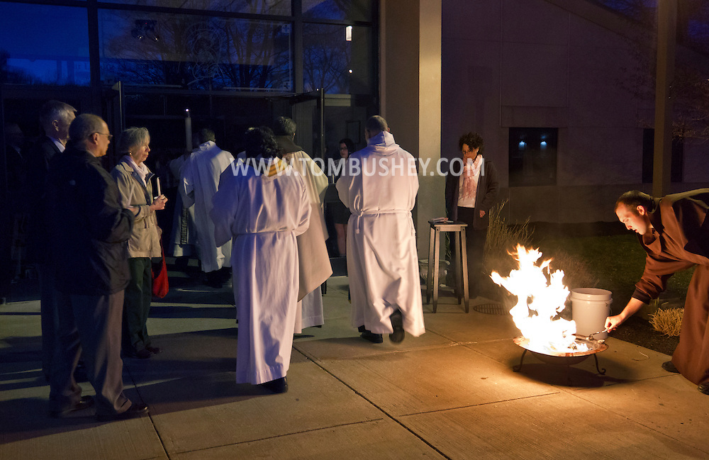 Middletown, New York - Parishioners and clergy enter Mount Carmel Church after the Easter Fire was used to light the Paschal Candle before the Easter Vigil Mass on April 7, 2012.