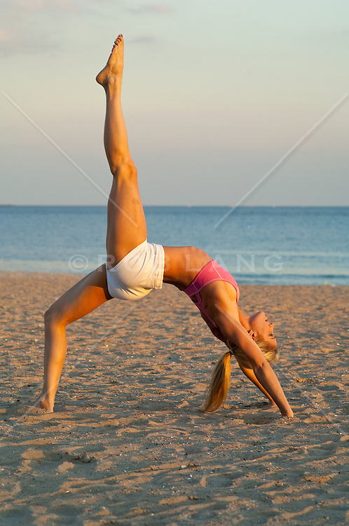 Blonde woman at the beach bent over backwards in a stretching yoga pose during a sunset at Coney Island, NY