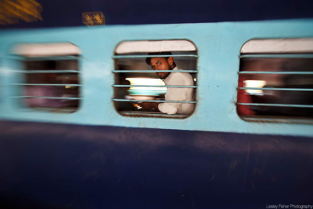 Man at the window of a departing train at New Delhi Train Station, Delhi, India