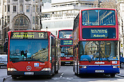 Public transport buses travel in heavy traffic in Trafalgar Square, London city centre, England, United Kingdom