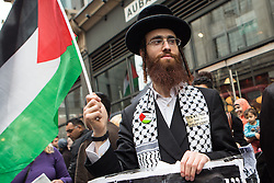 Image ©Licensed to i-Images Picture Agency. 11/07/2014. London, United Kingdom. Demonstration in London against Israeli strikes in Gaza. A Ultra-Orthodox Jew holds a palestinian flag in a demonstration against Israeli strikes in Gaza outside the Israeli embassy. Picture by Daniel Leal-Olivas / i-Images