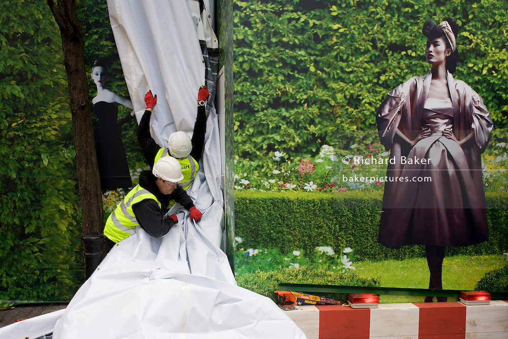 Workmen from Stewart Signs organise the hanging of a temporary printed media hanging outside a Dior shop being refurbished in central London.