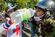 02 DECEMBER 2013 - BANGKOK, THAILAND: A volunteer medic rinses out the eyes of an anti-government rioter in Bangkok after police used tear gas on the crowd. Anti-government protestors and Thai police continued to face off Monday for a second day. Police used tear gas, water cannons and rubber bullets against protestors who charged their positions near the barriers on Chamai Maruchet bridge on Phitsanulok Road, which leads to the Government House.     PHOTO BY JACK KURTZ
