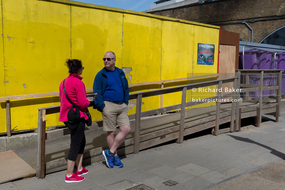 A couple wait for a bus against the background of a yellow construction hoarding on the Southbank, on 9th May 2018, in London, England.